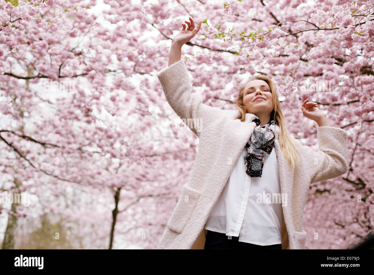 Young woman arms raised enjoying the fresh air in spring park. Carefree young female at spring blossom garden - Outdoors - Stock Image