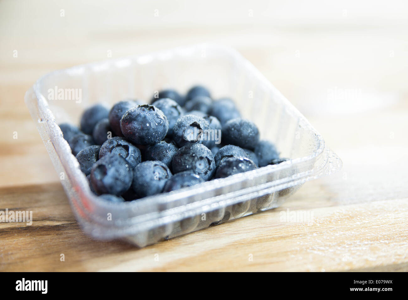 Blueberries on wooden table in plastic box. - Stock Image