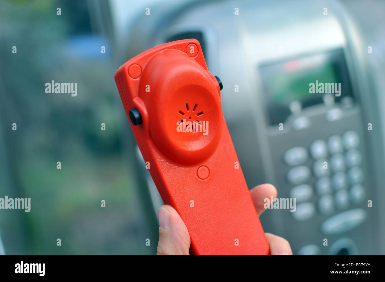Hand holding a red handset of a public telephone - Stock Image