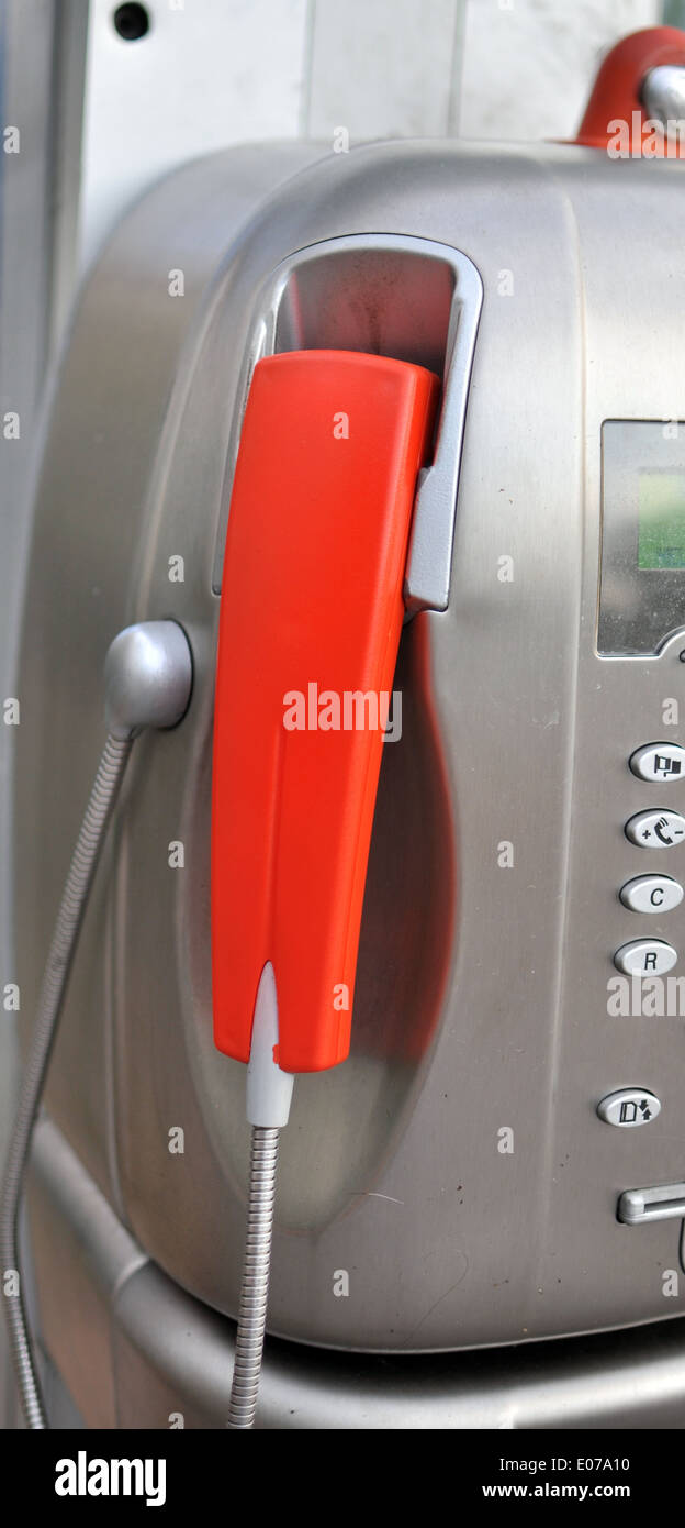red handset of a public telephone - Stock Image