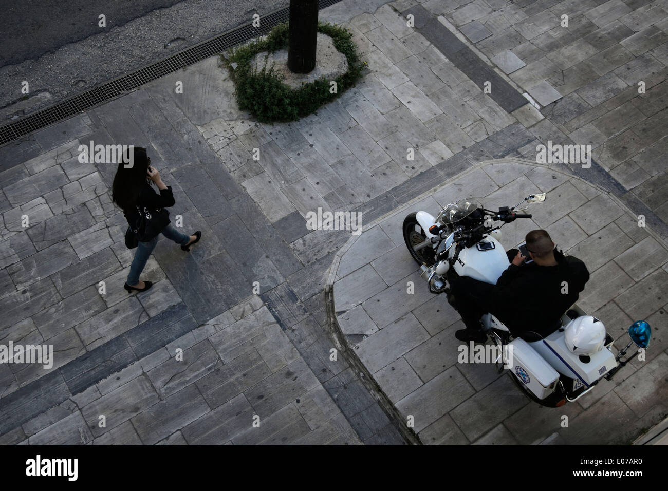 Athens, Greece. 5th May 2014. A woman walks past a police officer outside of the Athens Supreme court. Golden Dawn MPs were invited by the Special Appellate magistrate, to account for the category of membership and directing a criminal organization. Athens, Greece on May 5, 2014. Credit:  Konstantinos Tsakalidis/Alamy Live News - Stock Image
