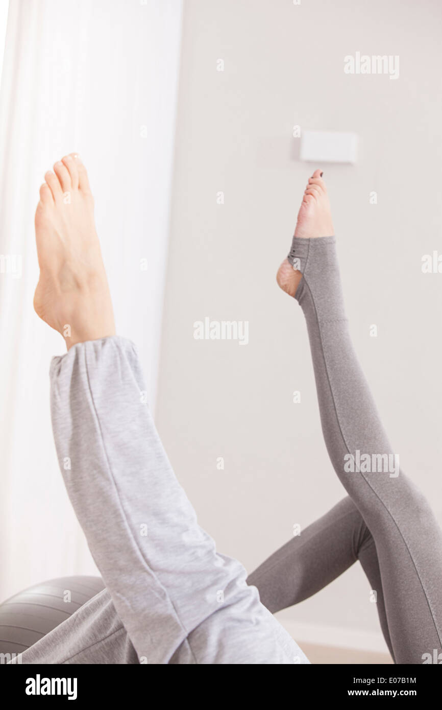 Two women doing Pilates exercise, feet up - Stock Image