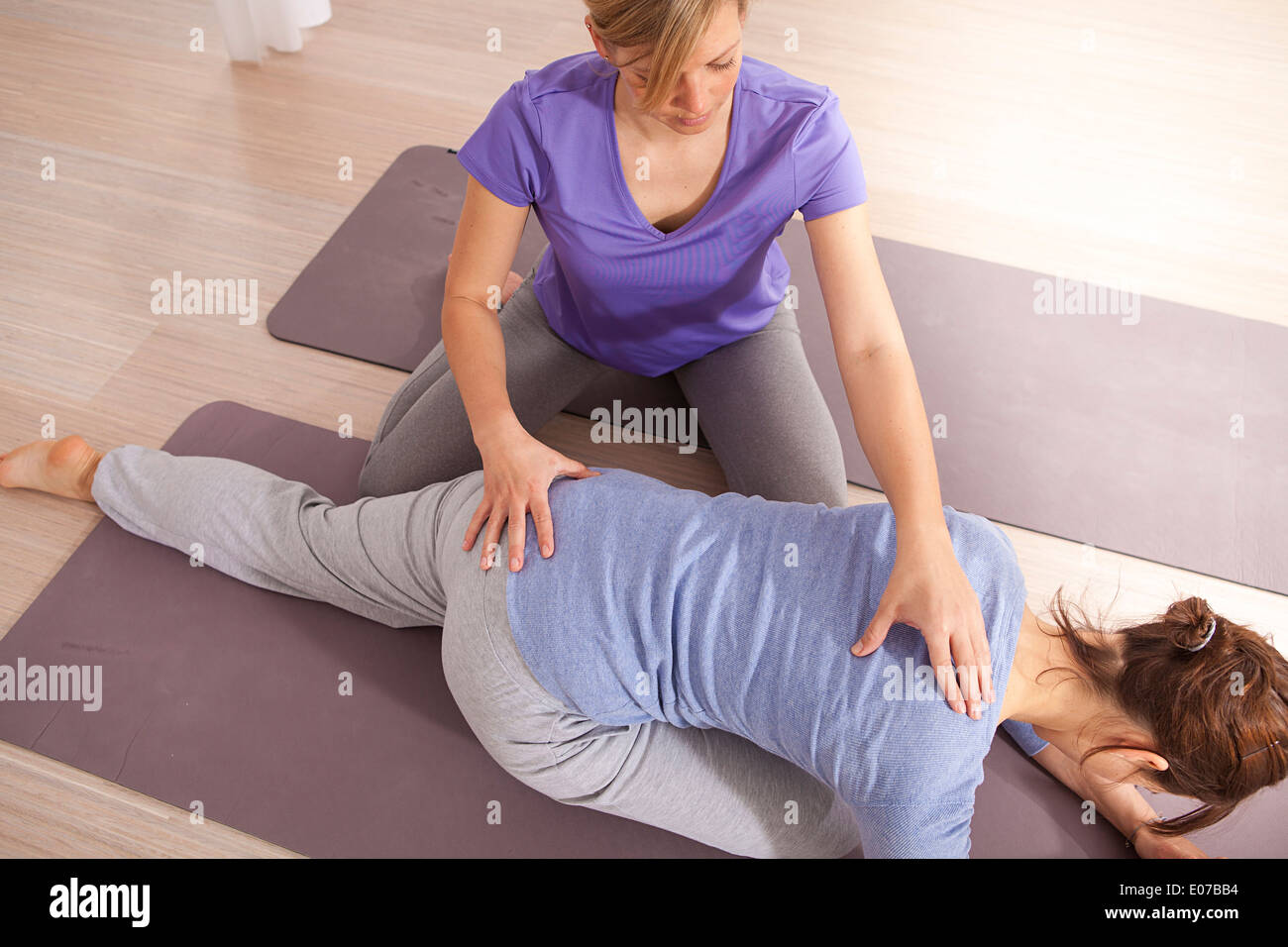 Physical therapist adjusting woman's back - Stock Image