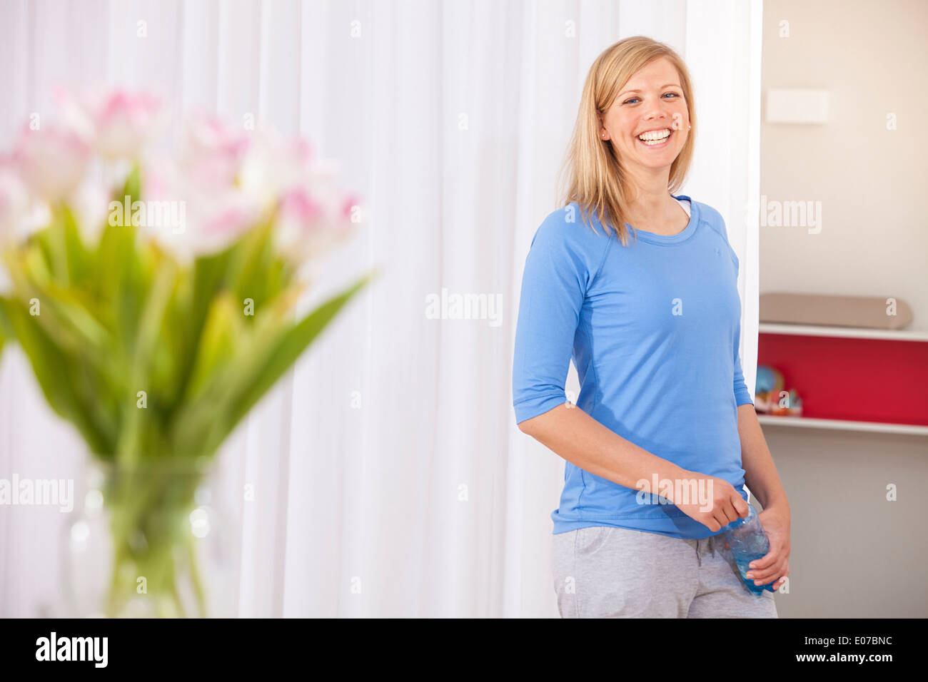 Blond woman in gym takes a break smiling cheerfully - Stock Image