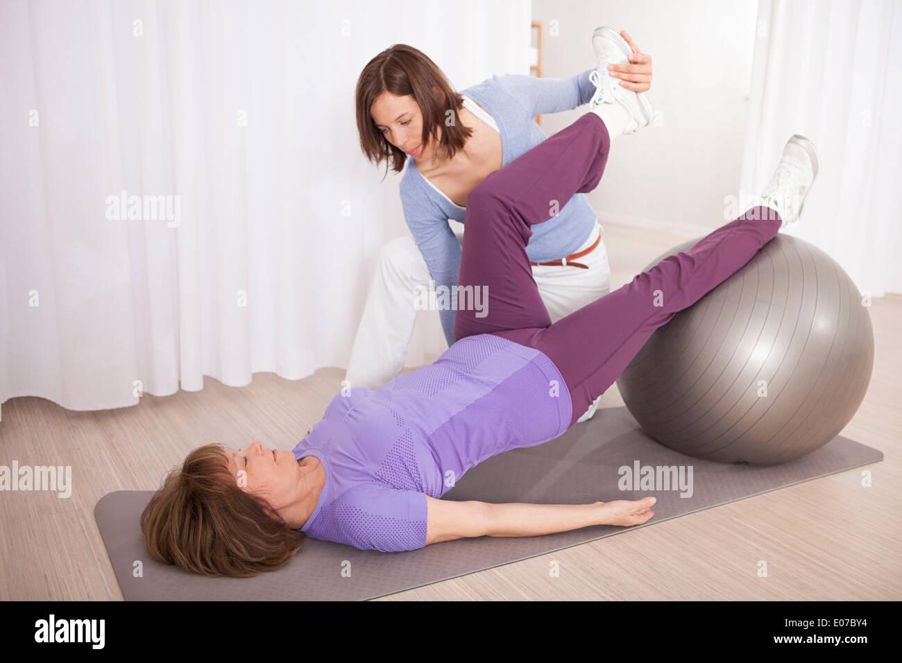 Senior woman adjusting woman's hip on exercise ball - Stock Image