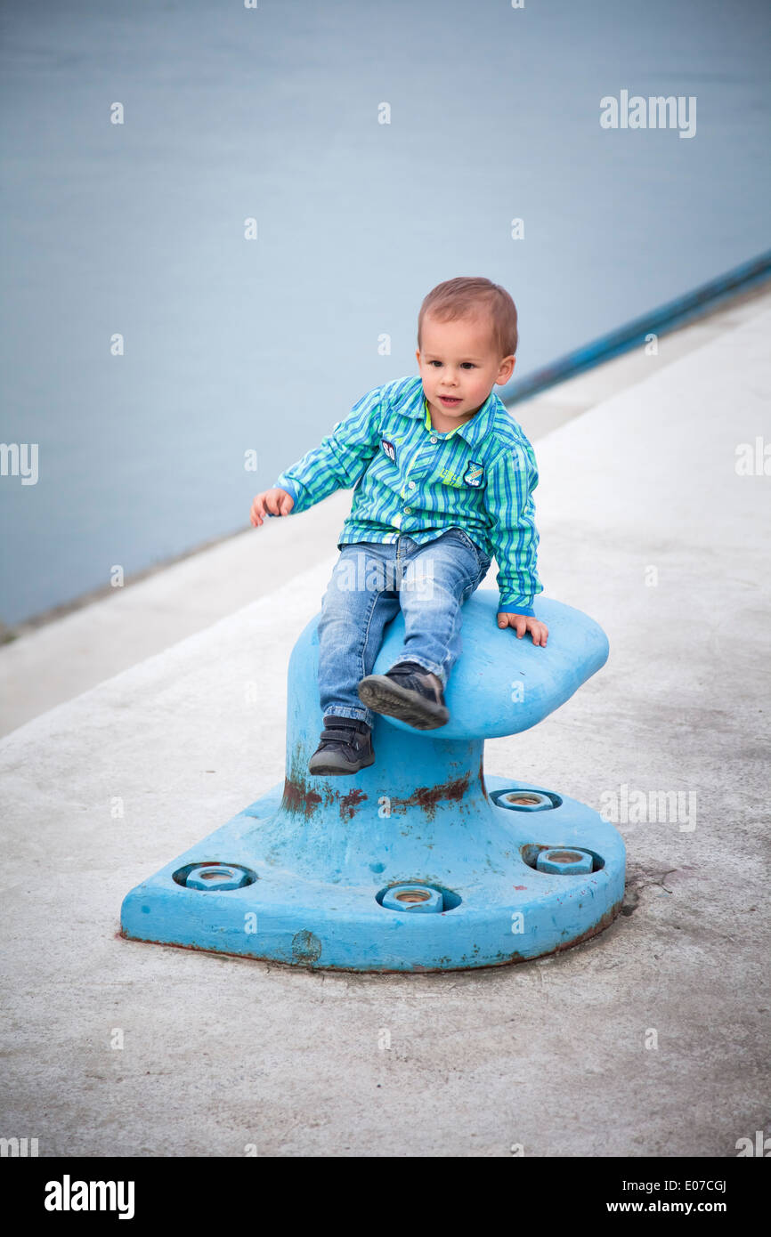 Toddler boy playing on a dock climbing a bollard, Austria - Stock Image