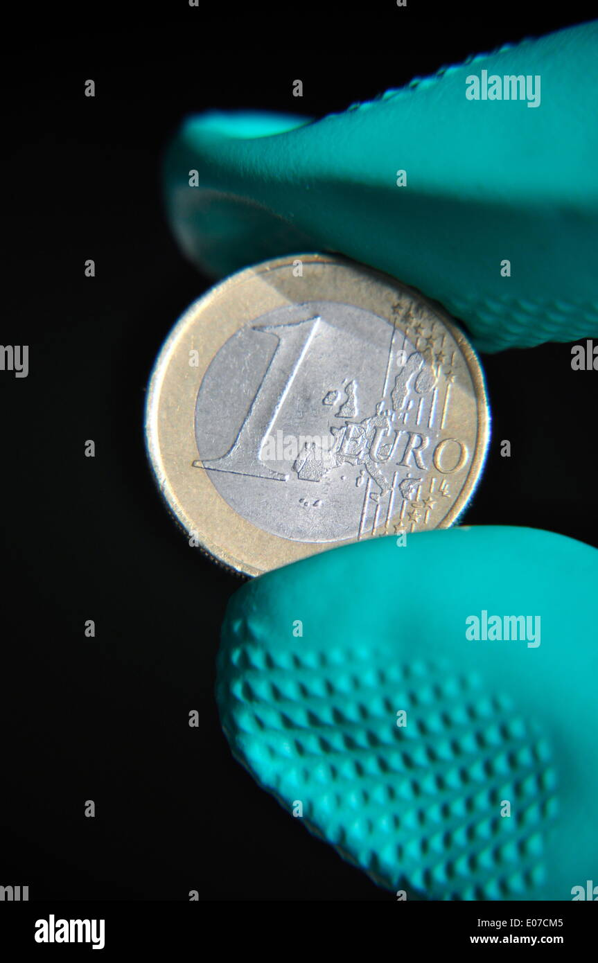 Illustration - a hand in a rubber glove holds a one euro coin in Germany, 08 October 2010. Photo: Berliner Verlag/Steinach - NO WIRE SERVICE - Stock Image