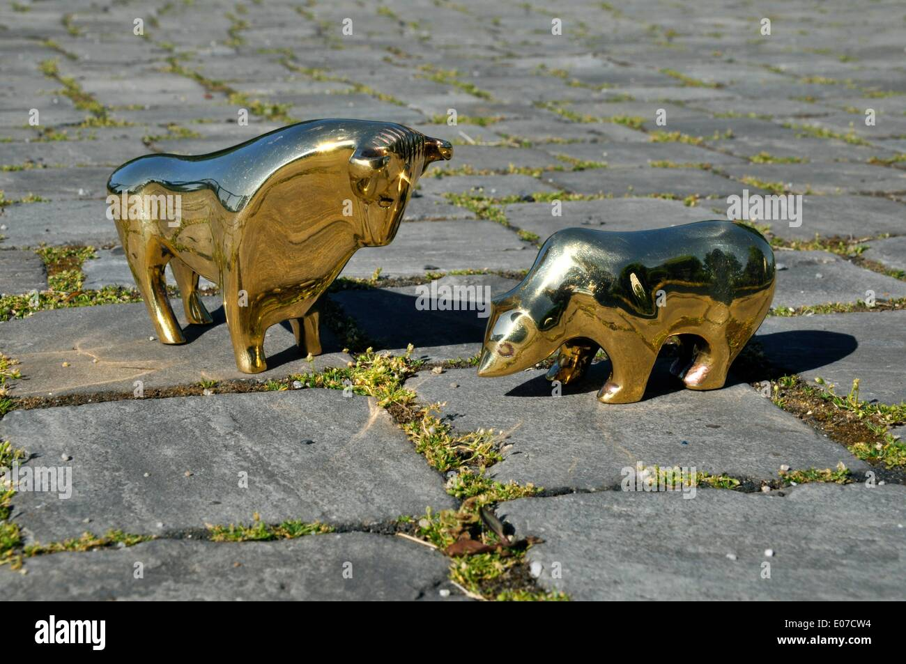 Illustration - Golden midget figures of the bear and the bull stand on a street in Germany, 02 June 2011. The bear Stock Photo