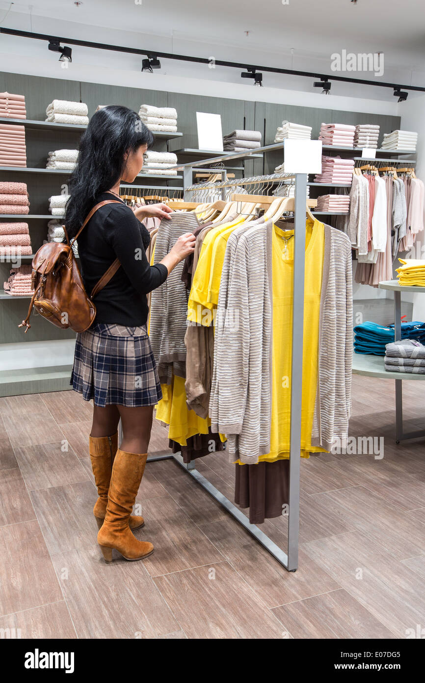 Woman shopping in clothes store - Stock Image