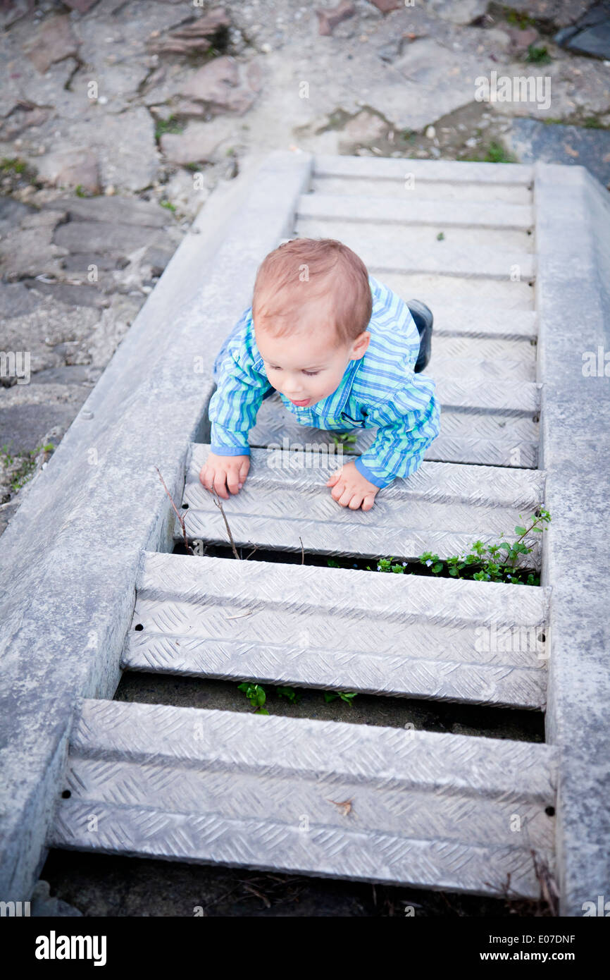 Toddler boy crawling upstairs, Austria - Stock Image