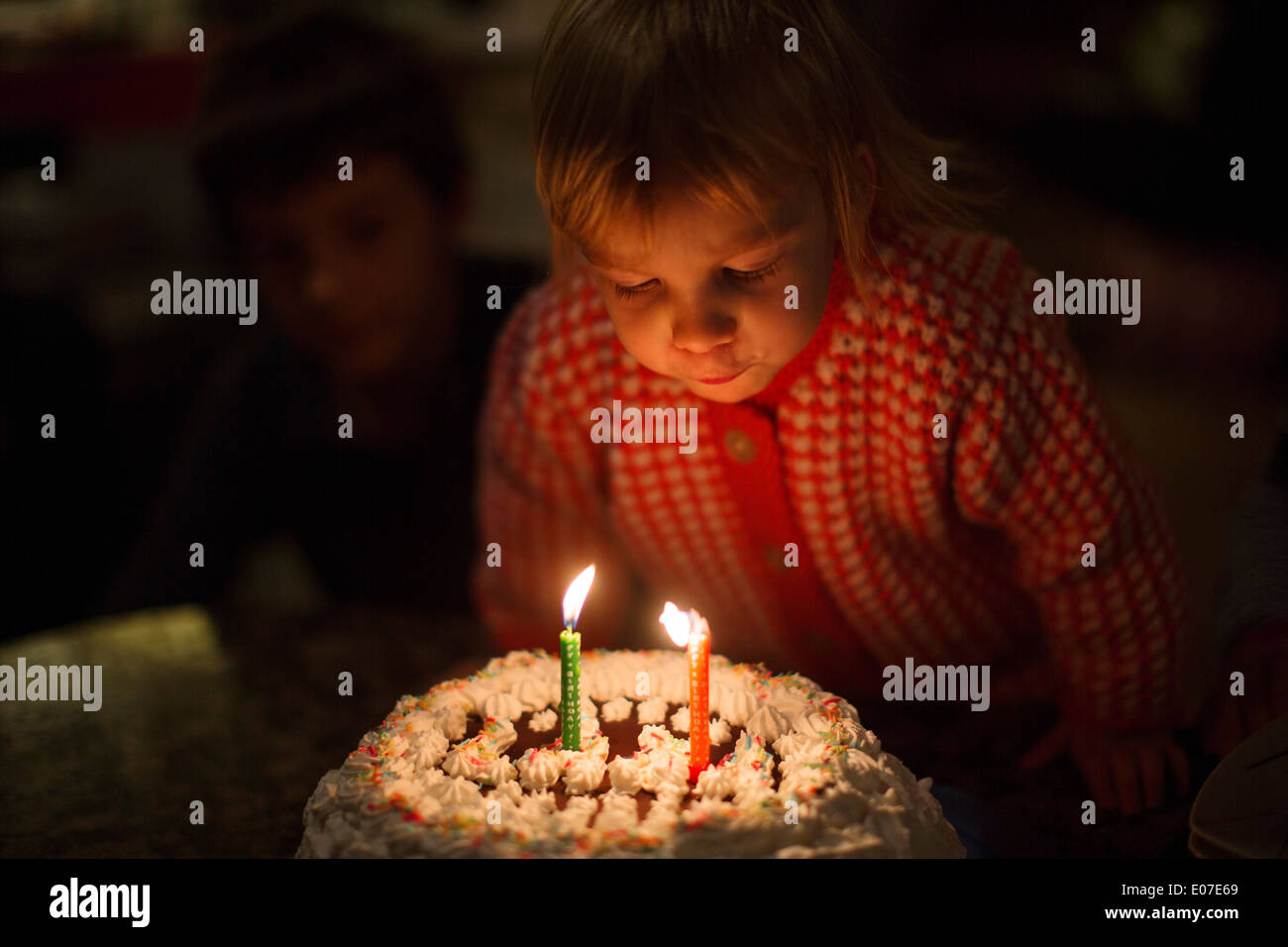 Little girl blowing out birthday candles on cake - Stock Image