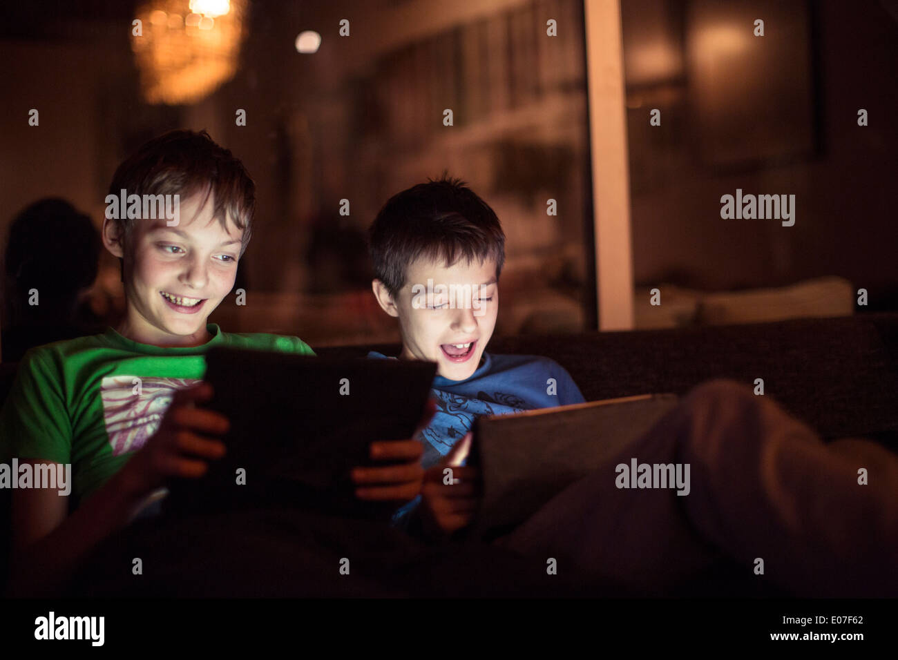 Two boys playing with digital tablets - Stock Image