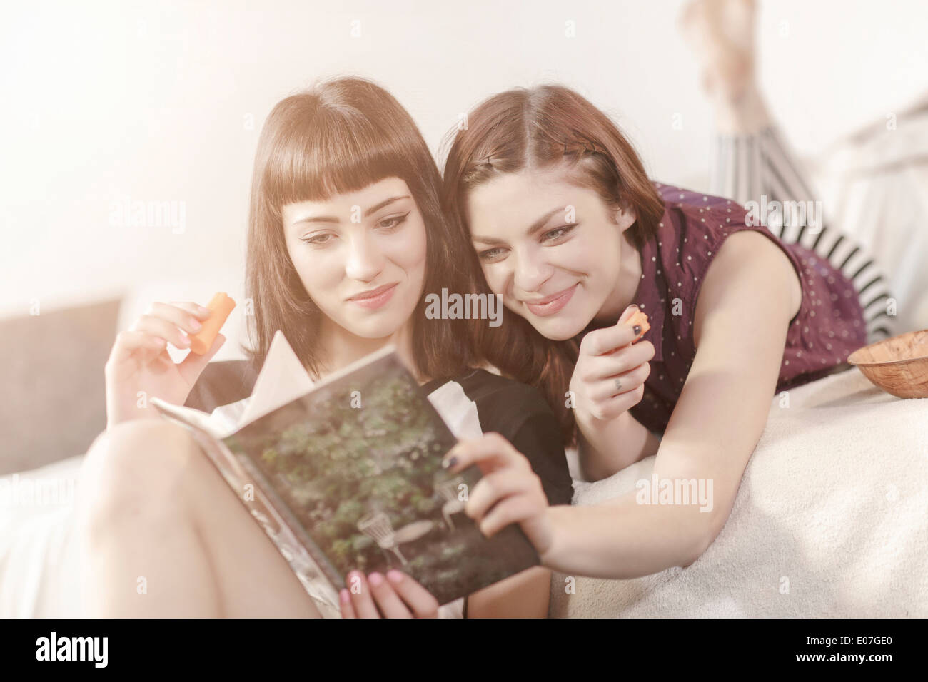 Two young women reading book together - Stock Image