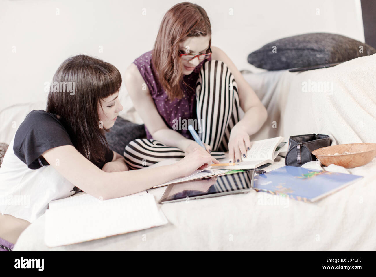 Two young women learning together with books and digital tablet - Stock Image