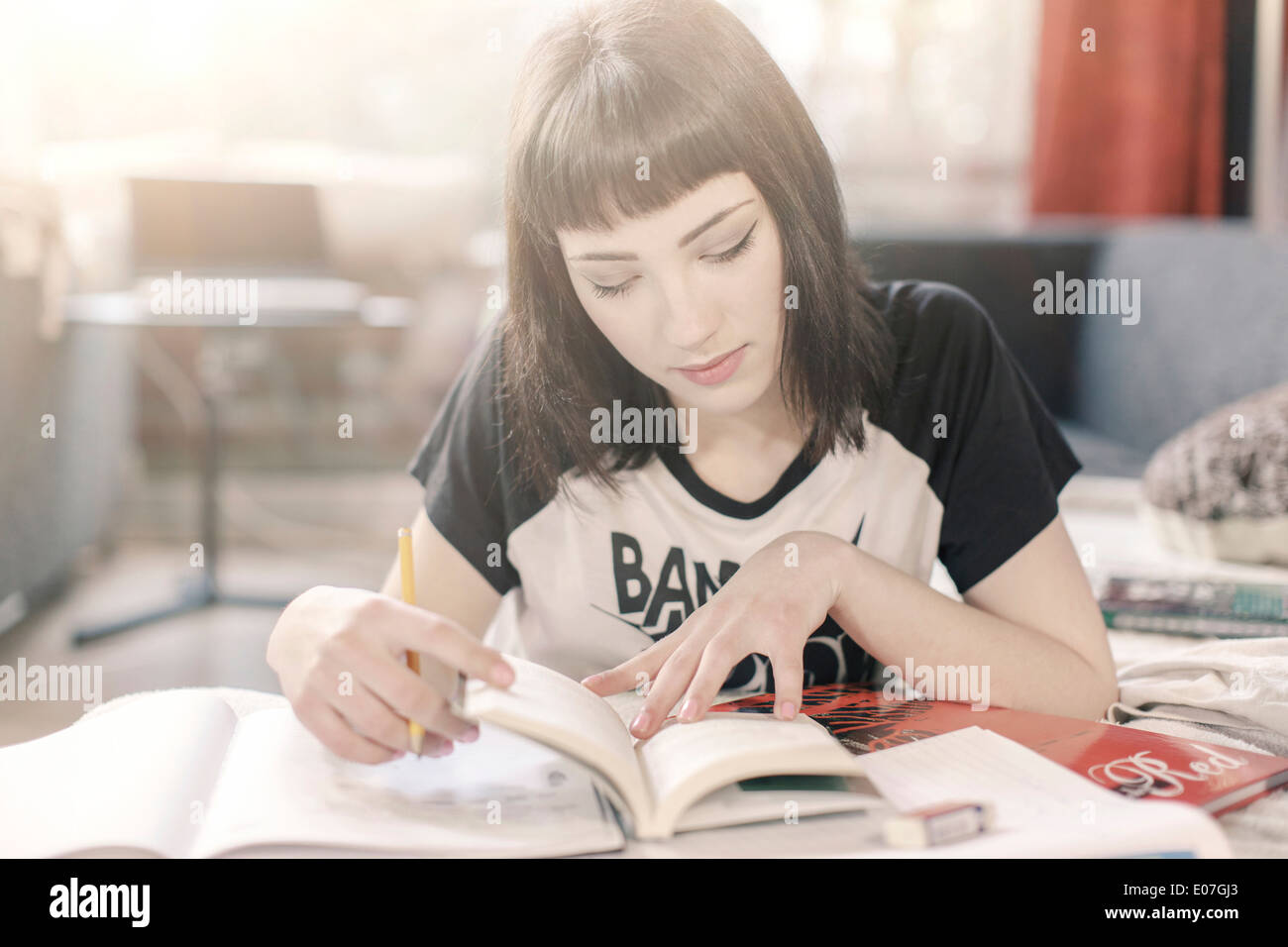 Young woman with brown hair reading in textbook - Stock Image
