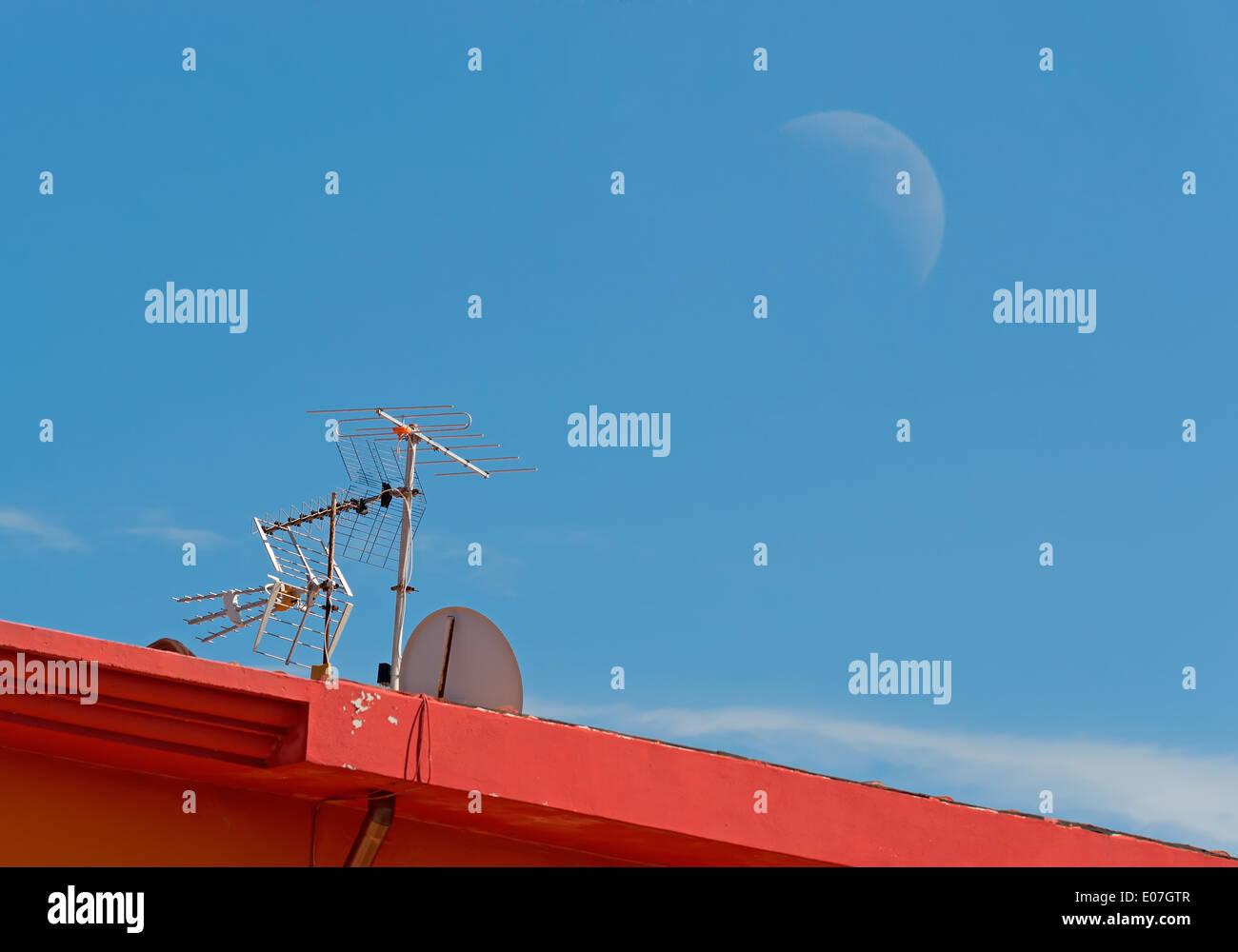 tv antenna under a huge moon - Stock Image