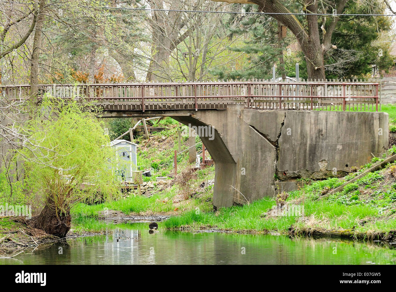Decaying bridge over channel leading to island. - Stock Image
