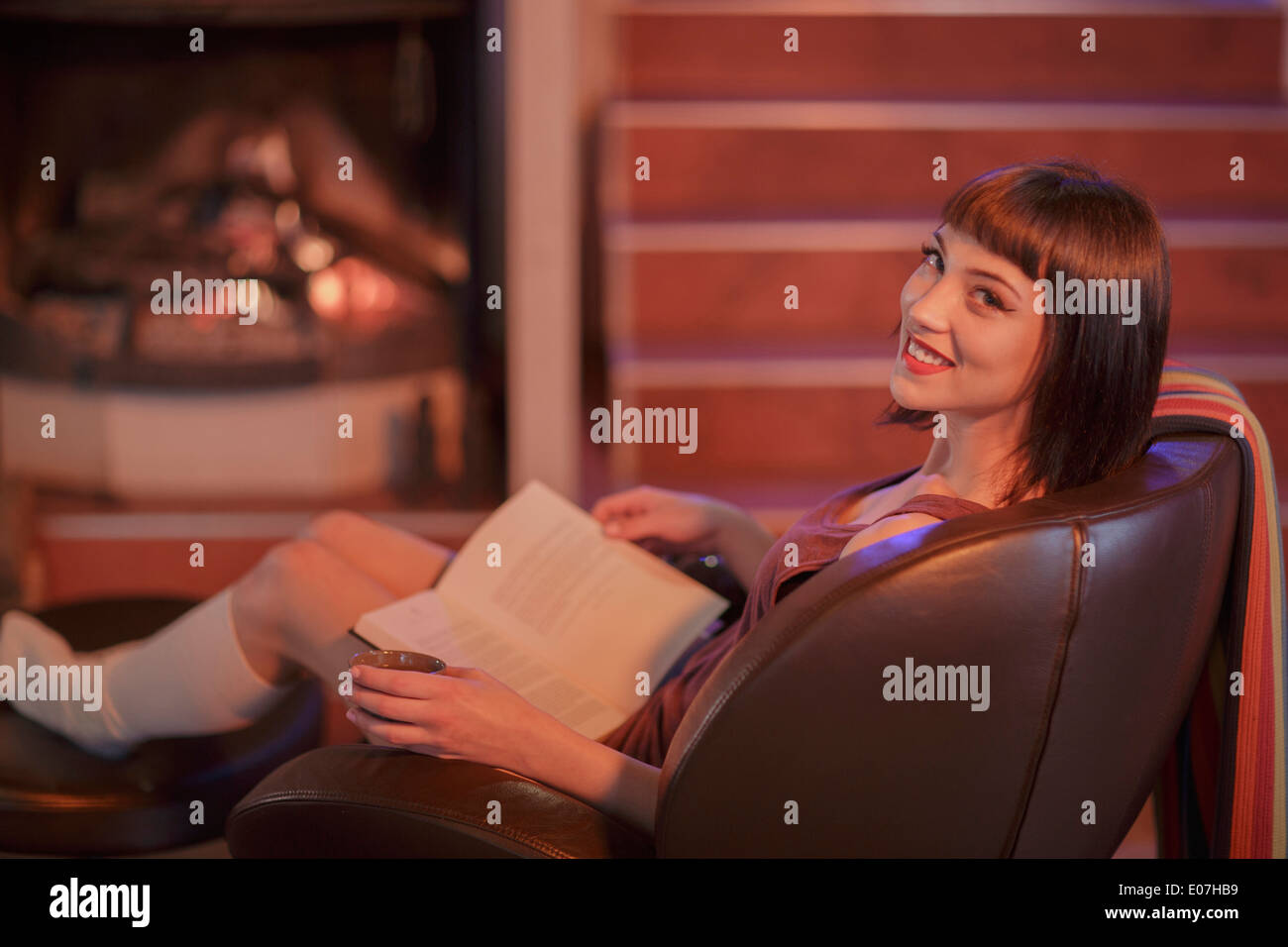 Young woman sits in armchair reading a book - Stock Image