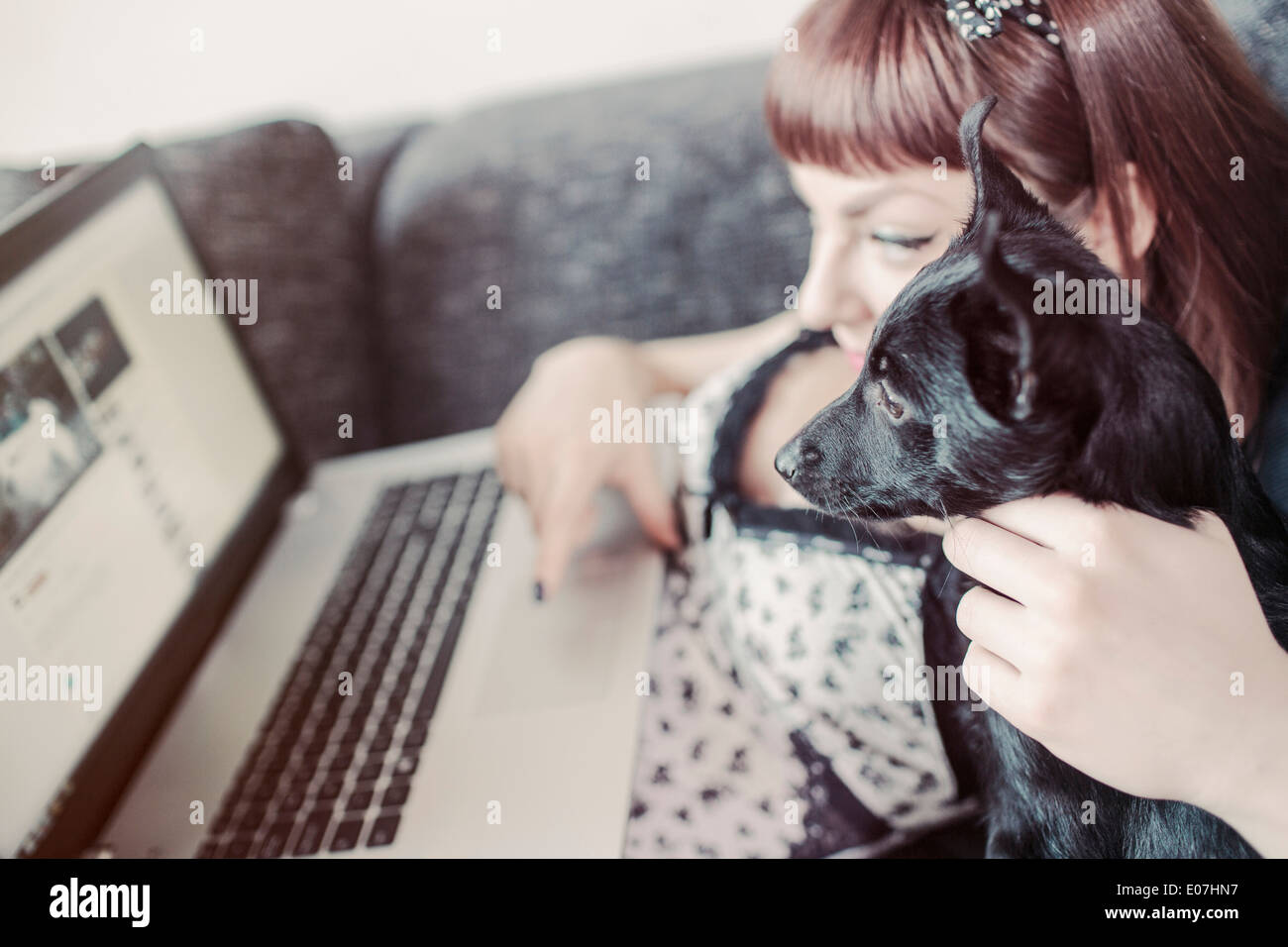 Young woman using laptop alongside her pet dog Stock Photo