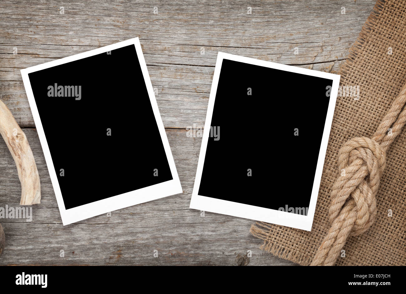 Blank photo frames with ship rope over wooden background Stock Photo