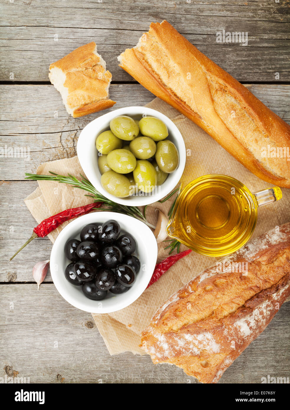 Italian food appetizer of olives, bread and spices on wooden table background - Stock Image
