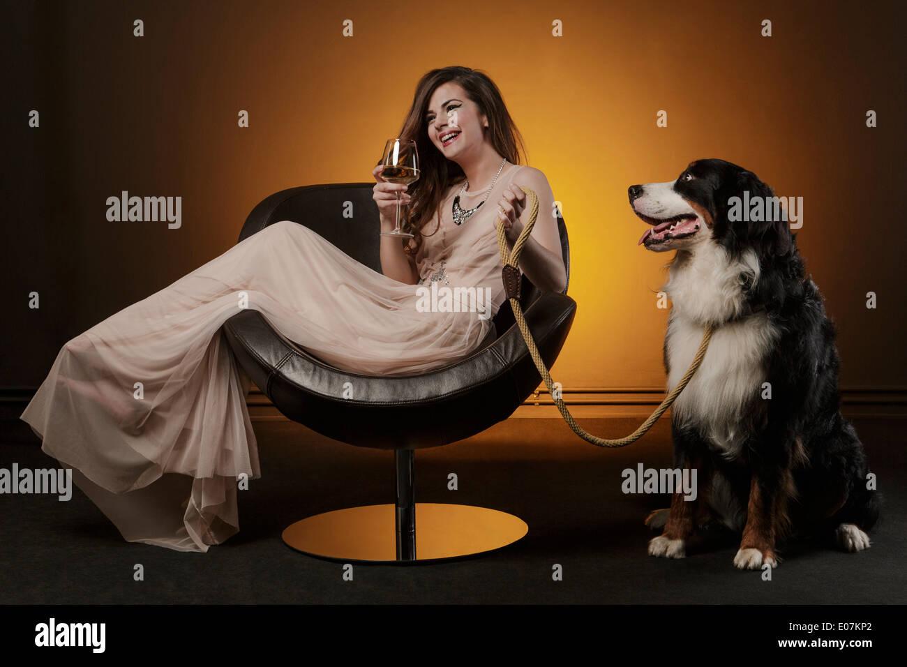 Woman drinking a glass of wine alongside huge dog - Stock Image