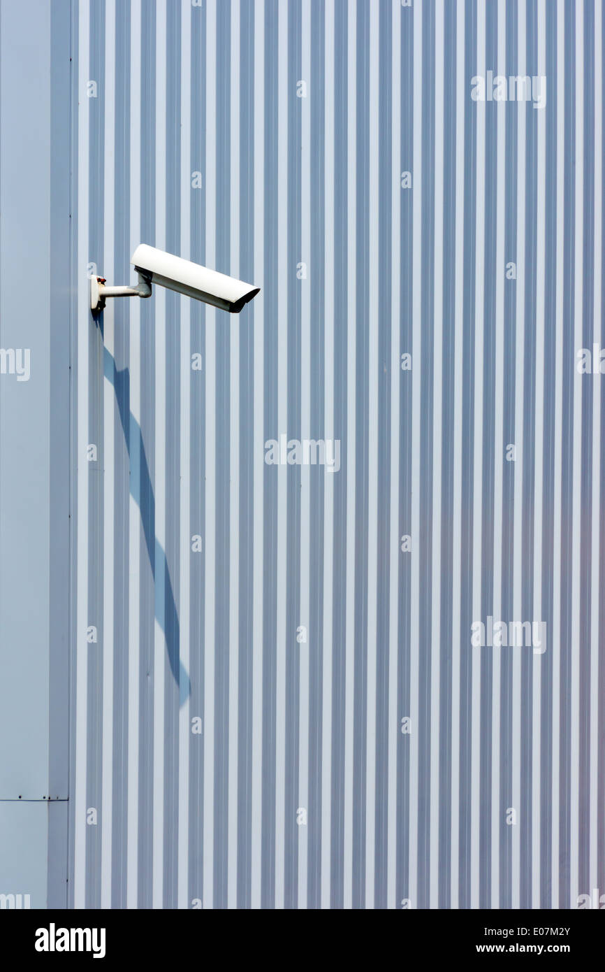 surveillance security camera on industrial wall - Stock Image