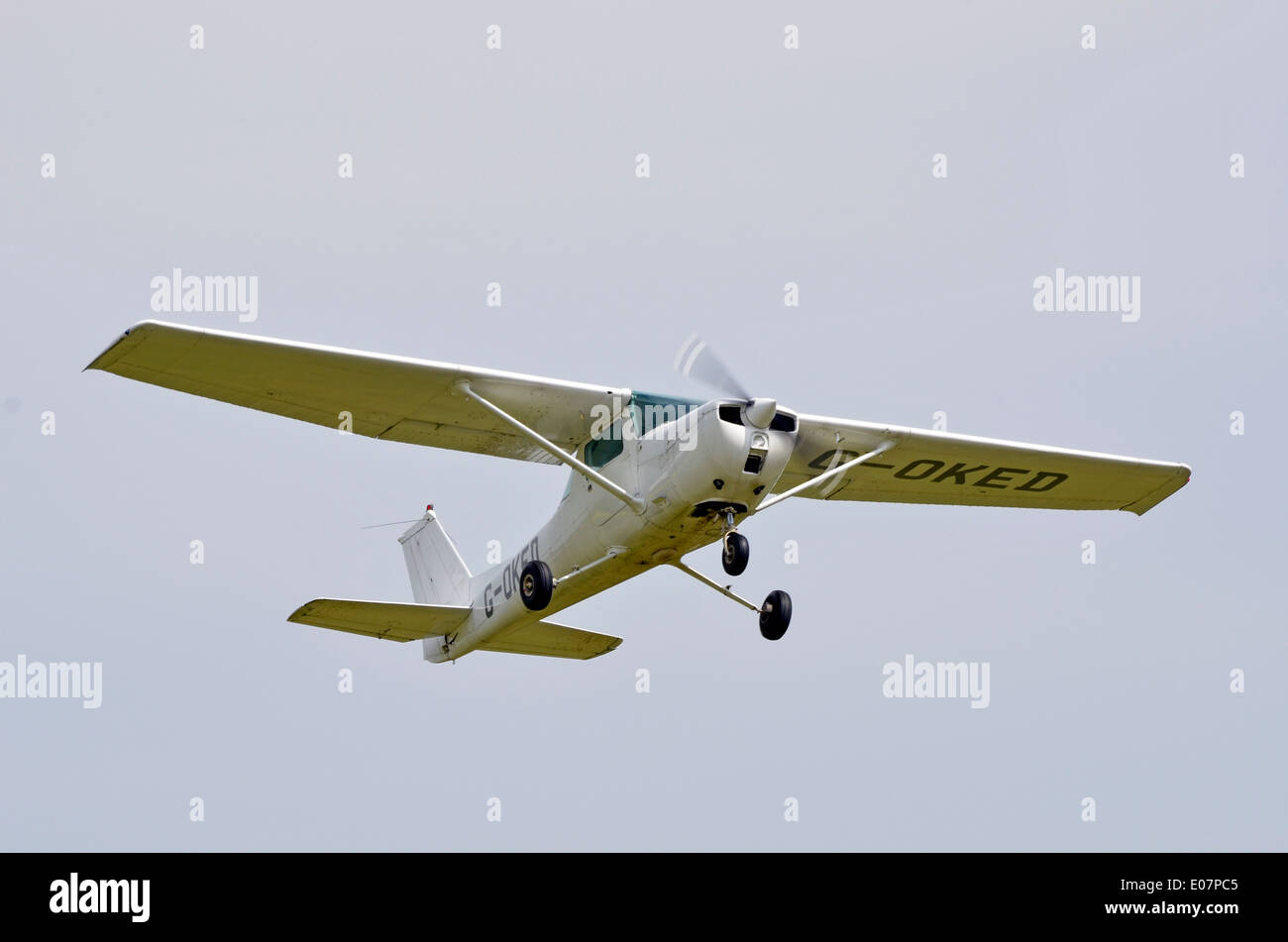 Cessna 150L high wing monoplane light aircraft climbs out after taking off from Popham Airfield, Hamsphire, England - Stock Image