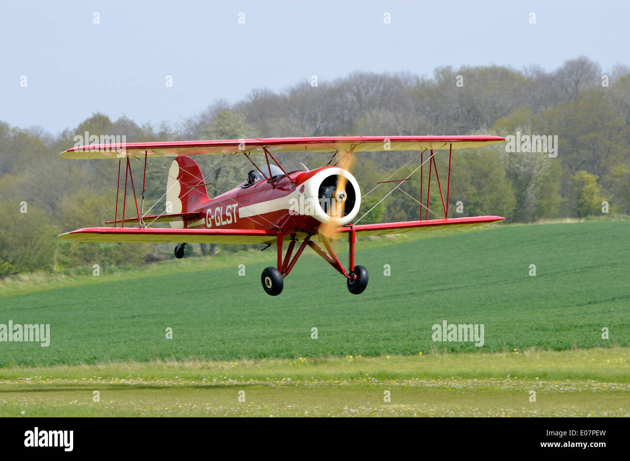 Replica Great Lakes Sports Trainer biplane, G-GLST taking off from the grass airstrip at Popham Airfield, Hampshire - Stock Image