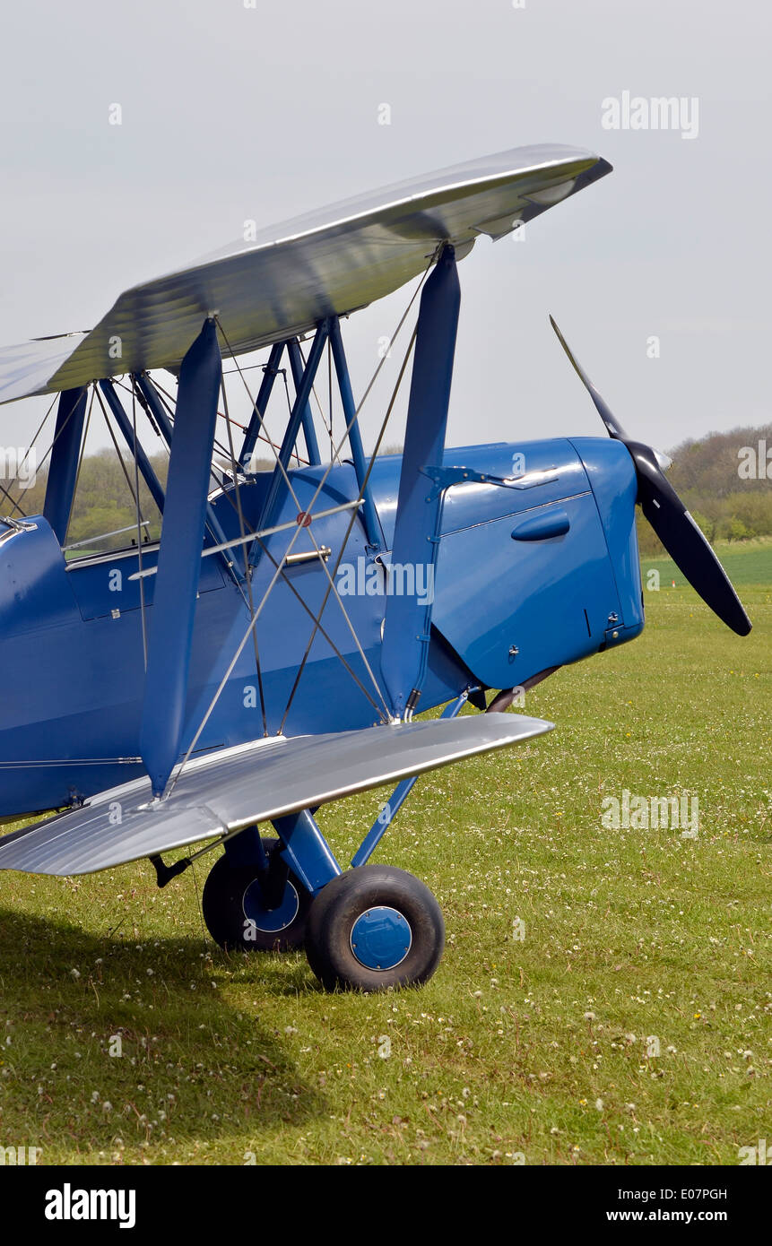Blue  de Havilland DH.82 Tiger Moth biplane on a grass airstrip in Hampshire, England. - Stock Image