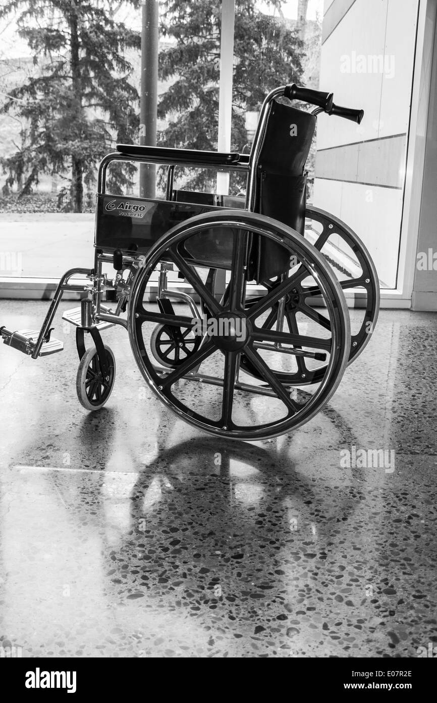Empty Wheelchair with Reflection Pointed Towards Outdoors - Stock Image