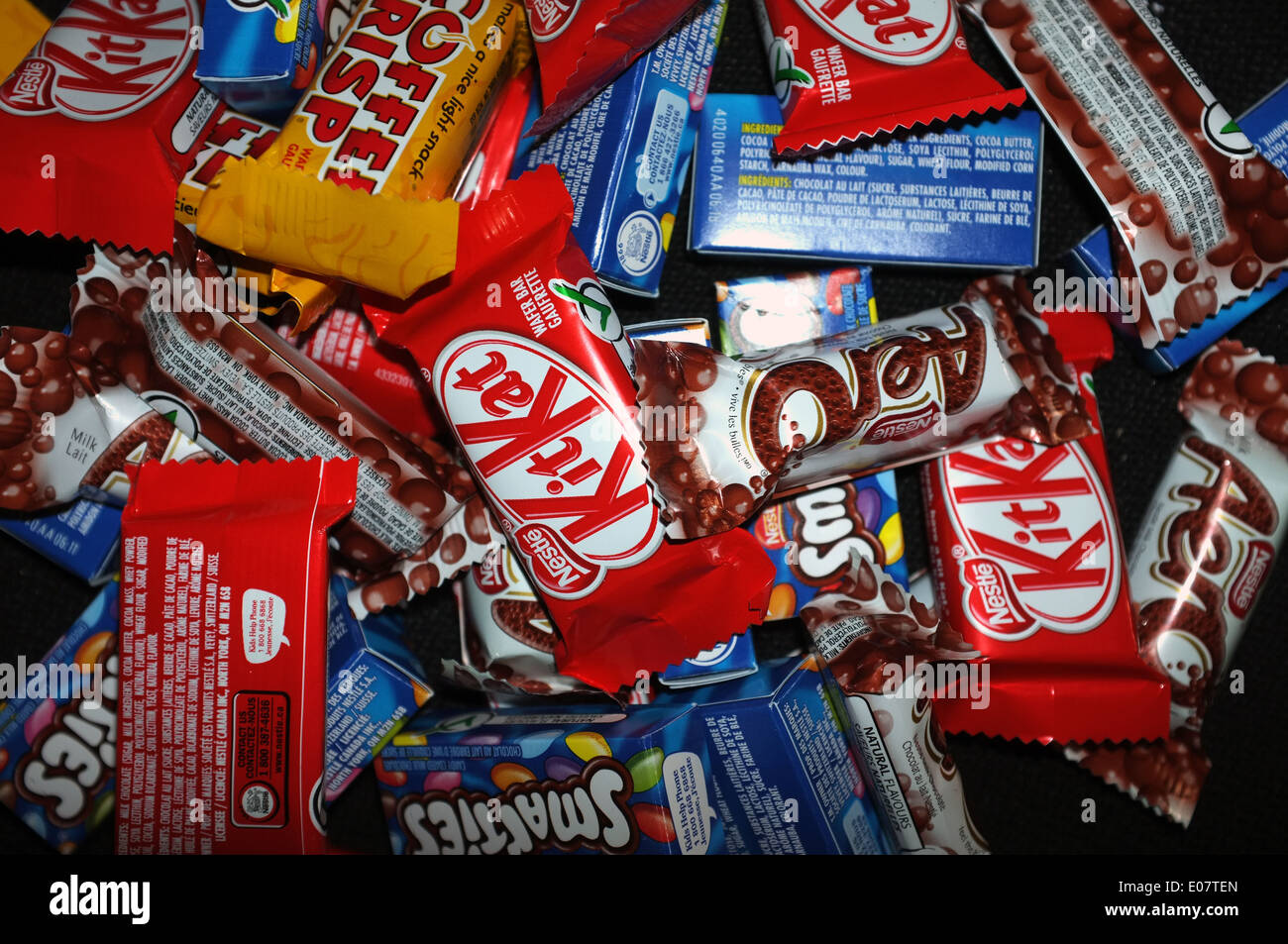 Aero, Coffee Crisp, Kit Kat and Smarties chocolates photographed against a black background. - Stock Image