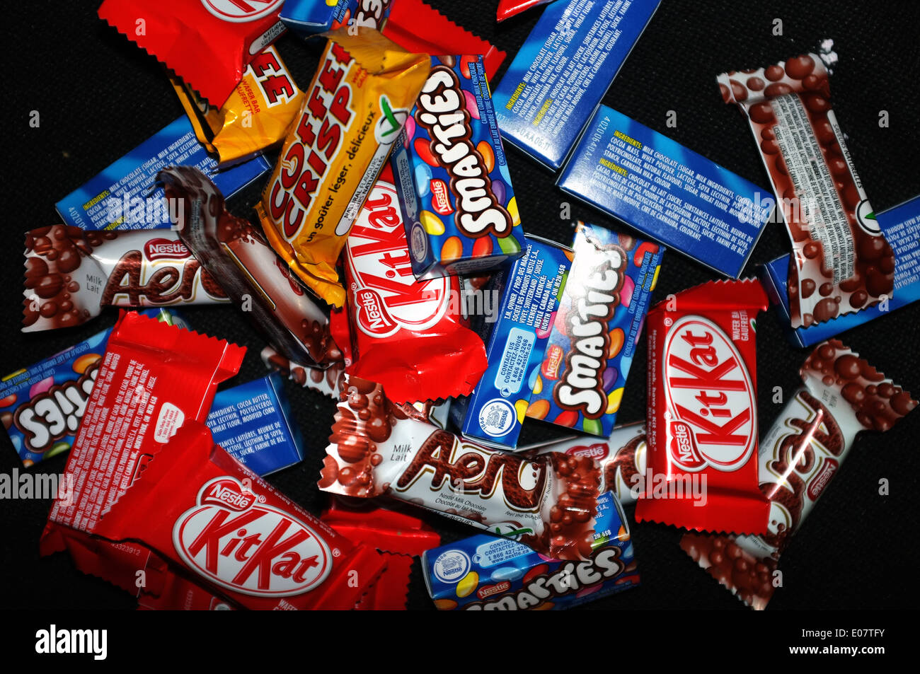 A pile of Aero, Coffee Crisp, Kit Kat and Smarties chocolates photographed against a black background. - Stock Image