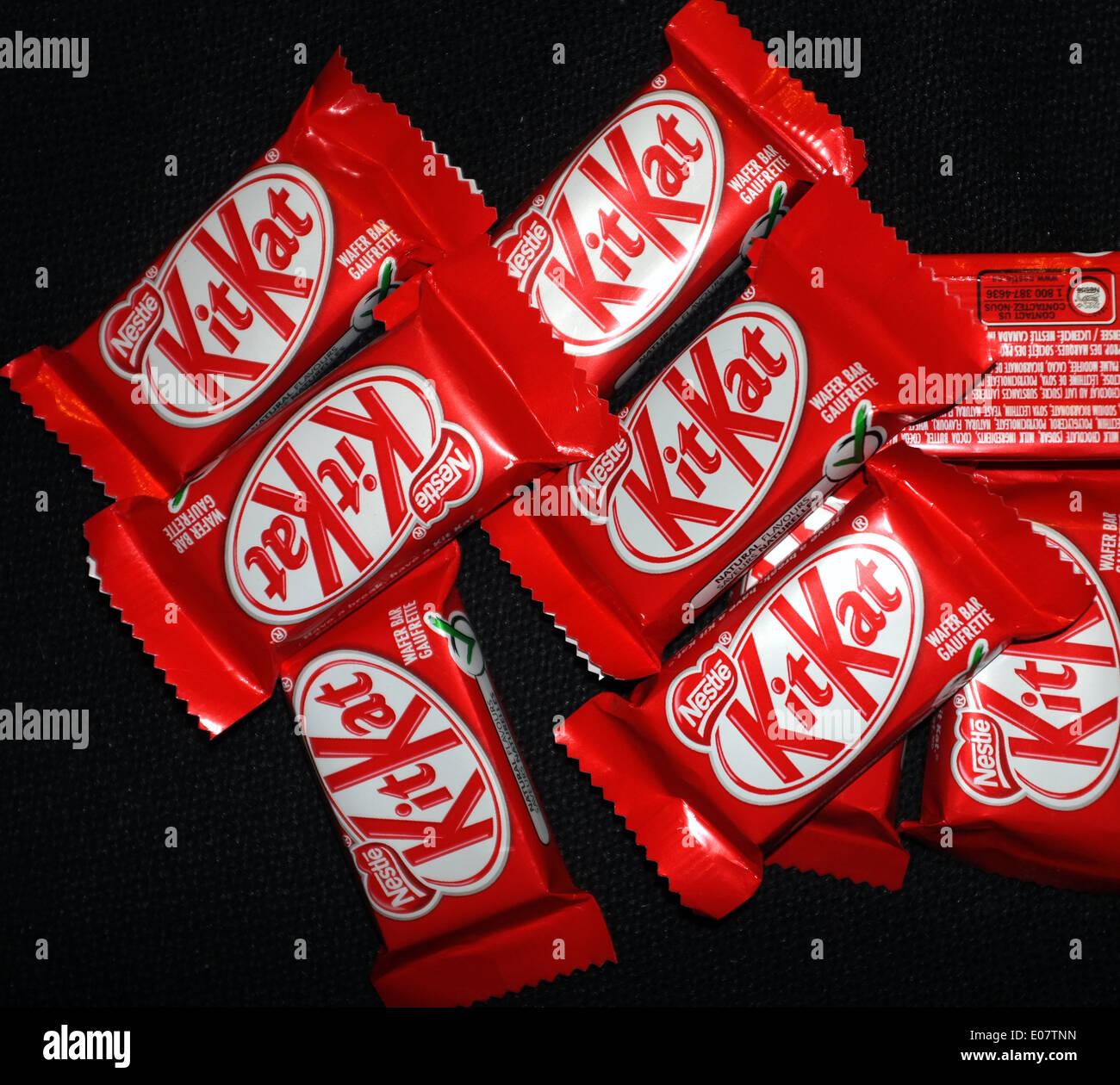 Kit Kat chocolates photographed against a black background. - Stock Image