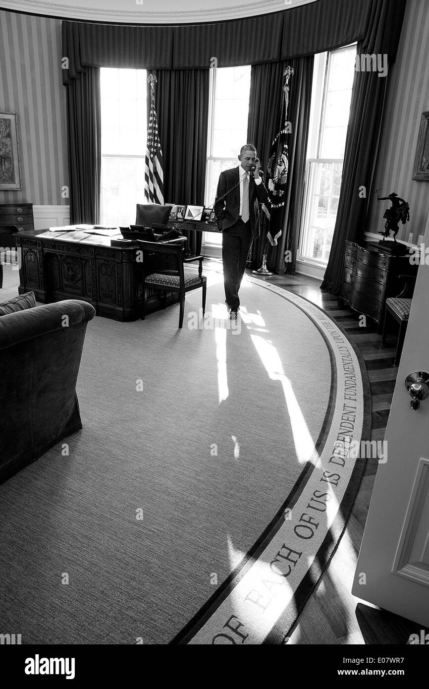 US President Barack Obama talks on the phone with Prime Minister David Cameron of the United Kingdom from the Oval Office of the White House January 16, 2014 in Washington, DC. - Stock Image