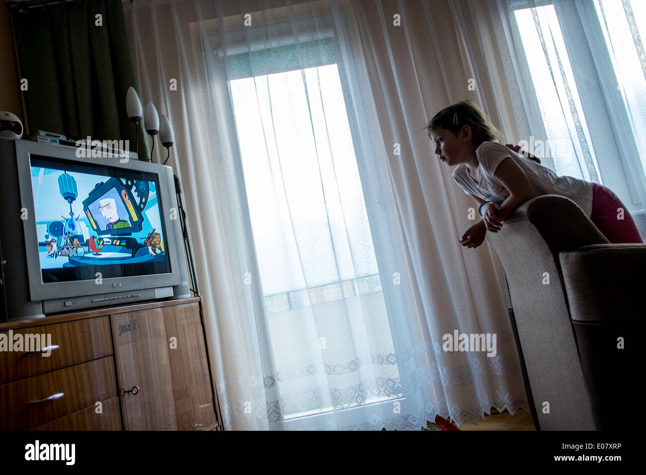 Gir age 5,6,7 at home watching TV, Starachowice, Poland - Stock Image