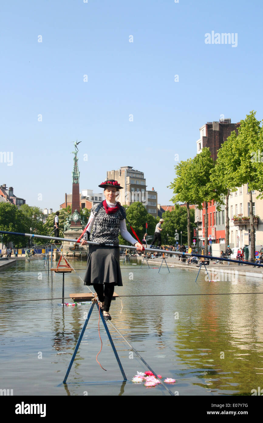 Tightrope walker in Brussels going across water fountain pool - Stock Image