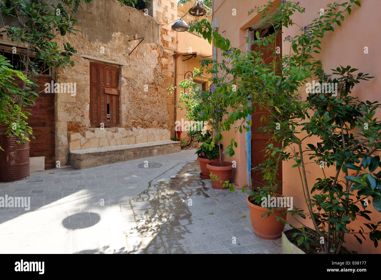 Narrow stone tiled alleyway lined with colourful facades pot plants back street old town Chania Crete Greece - Stock Image