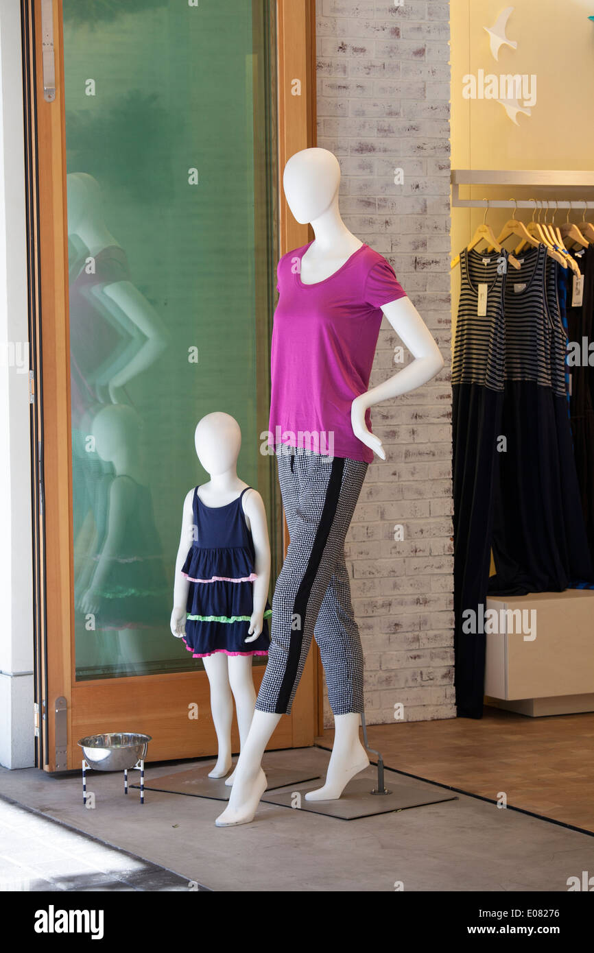 A woman with daughter set of mannequins display the latest fashions at a woman's clothing store. - Stock Image