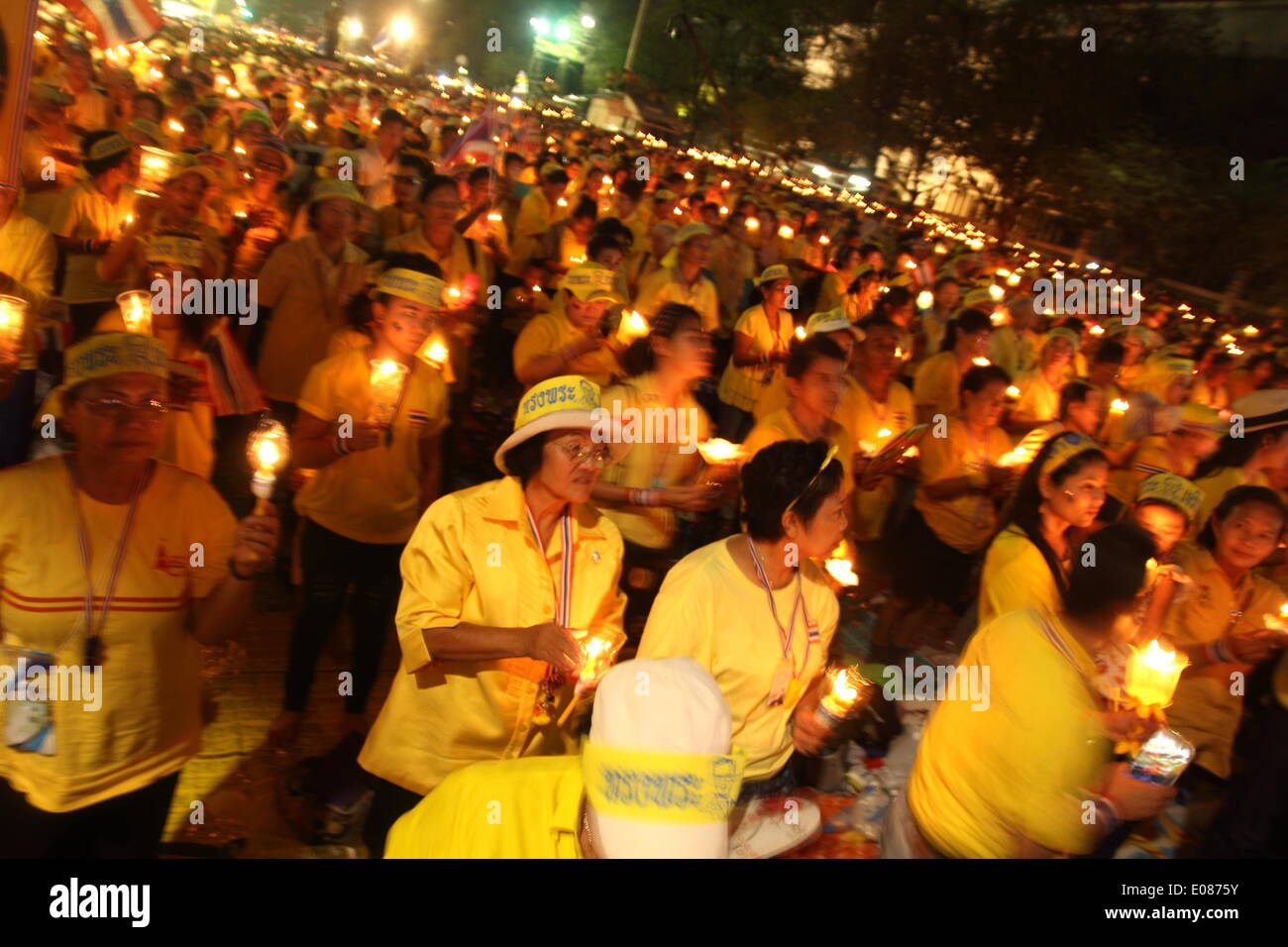 Bangkok, Thailand. 5th May 2014. Anti-government protesters hold candles during a ceremony showing their loyalty to King Bhumibol Adulyadej on the 64th anniversary of his Coronation Day. Anti-government protesters gathered close to the Grand Palace on Coronation Day. Thailand's revered King Bhumibol Adulyadej made a rare public appearance to mark the 64th anniversary of his coronation. Credit:  Sanji Dee/Alamy Live News - Stock Image