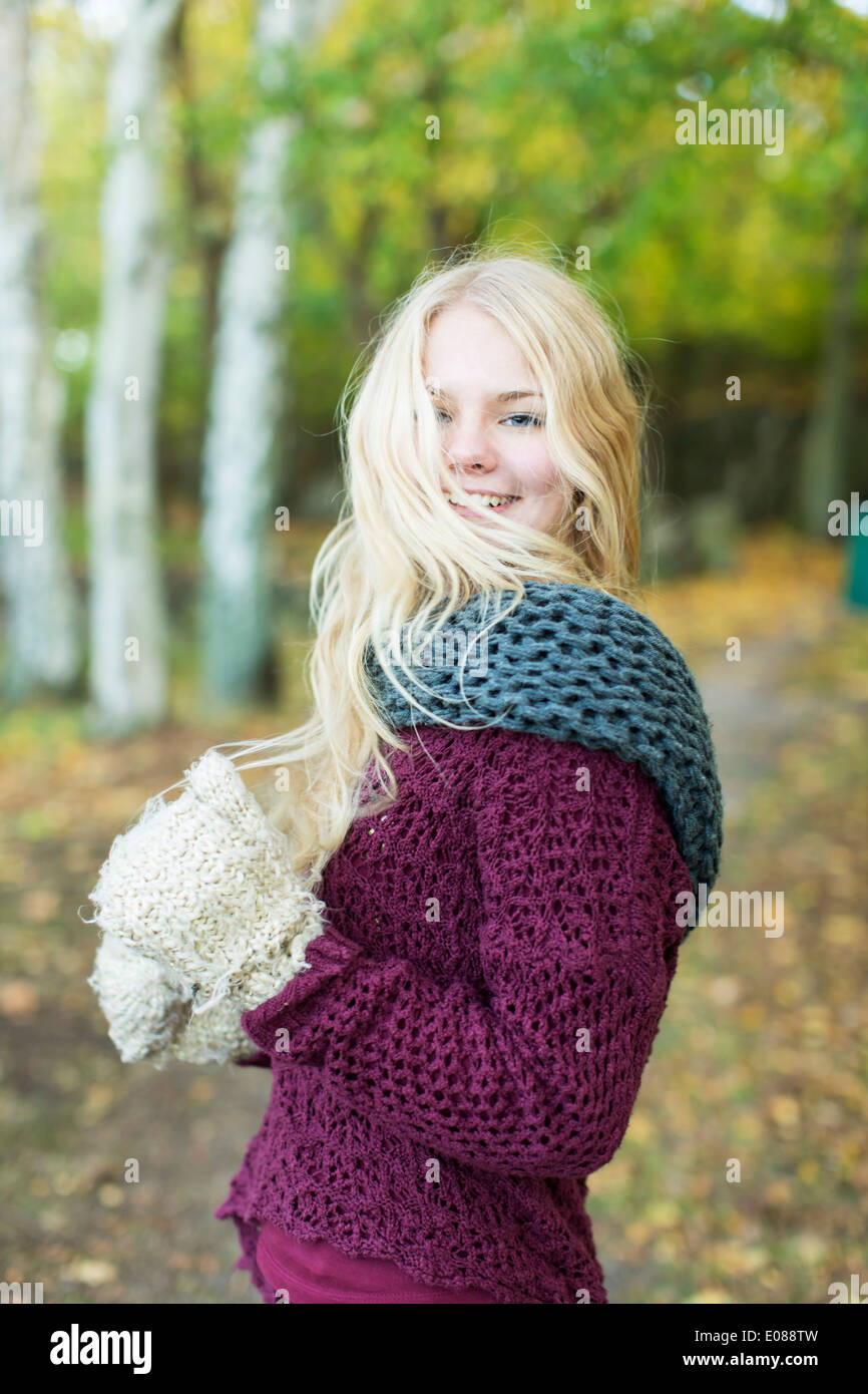 Portrait of happy teenage girl in winter wear outdoors - Stock Image