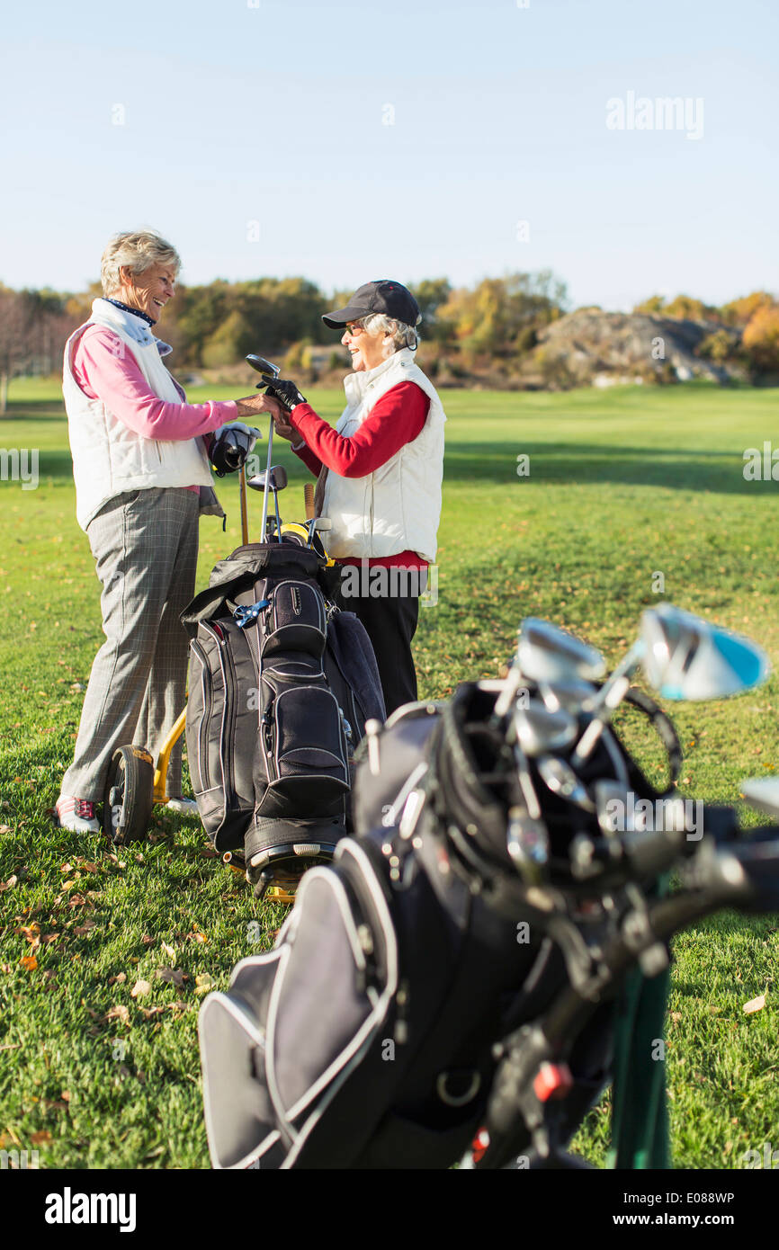 Side view of senior female friends choosing golf club on golf course - Stock Image