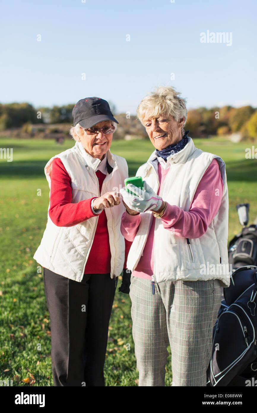 Senior female golfers using mobile phone on golf course - Stock Image