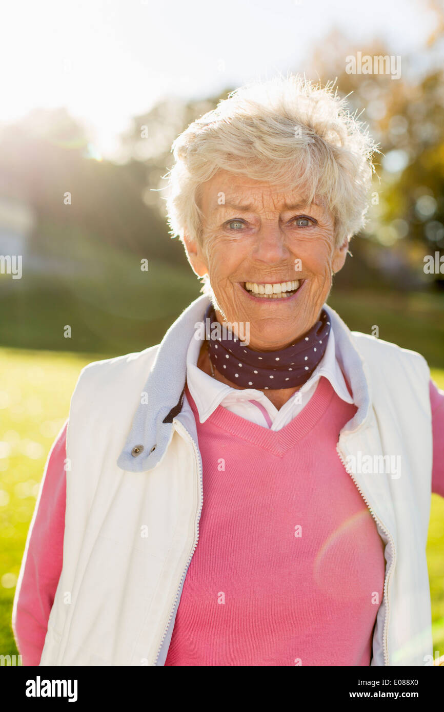 Portrait of senior woman smiling outdoors - Stock Image