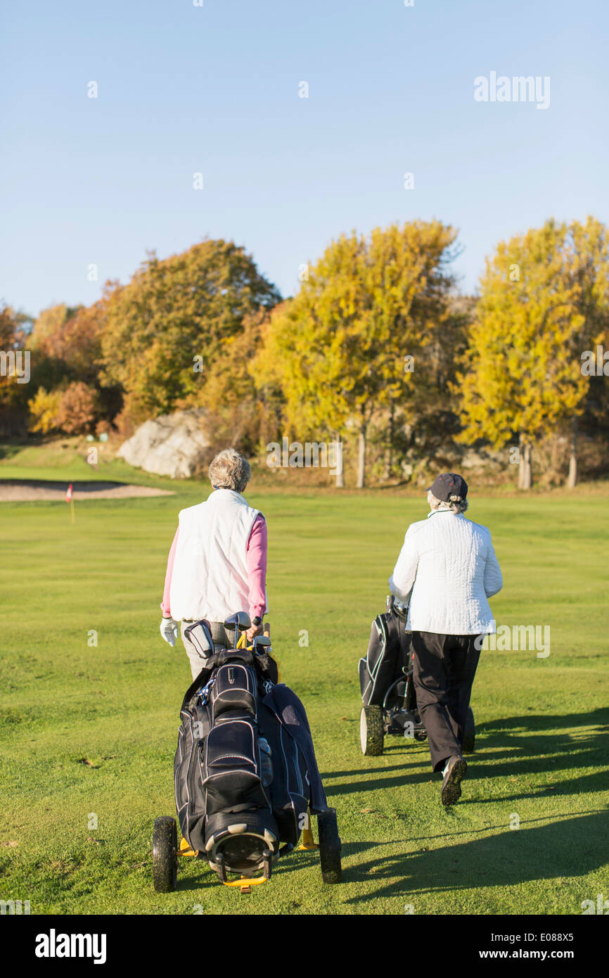 Rear view of senior women walking with golf bags on course - Stock Image