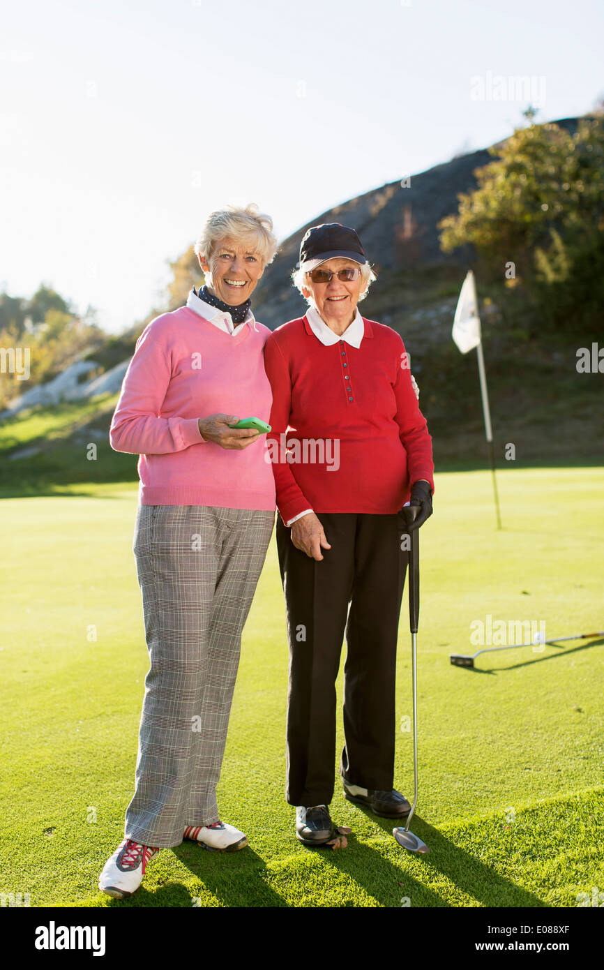 Full length portrait of senior female golfers standing on golf course - Stock Image