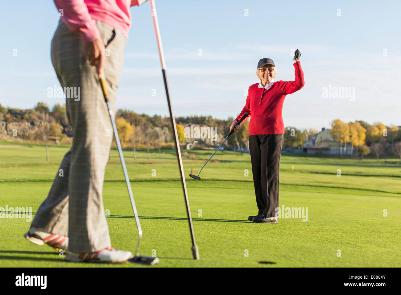 Full length of successful female golfer with friend on golf course - Stock Image