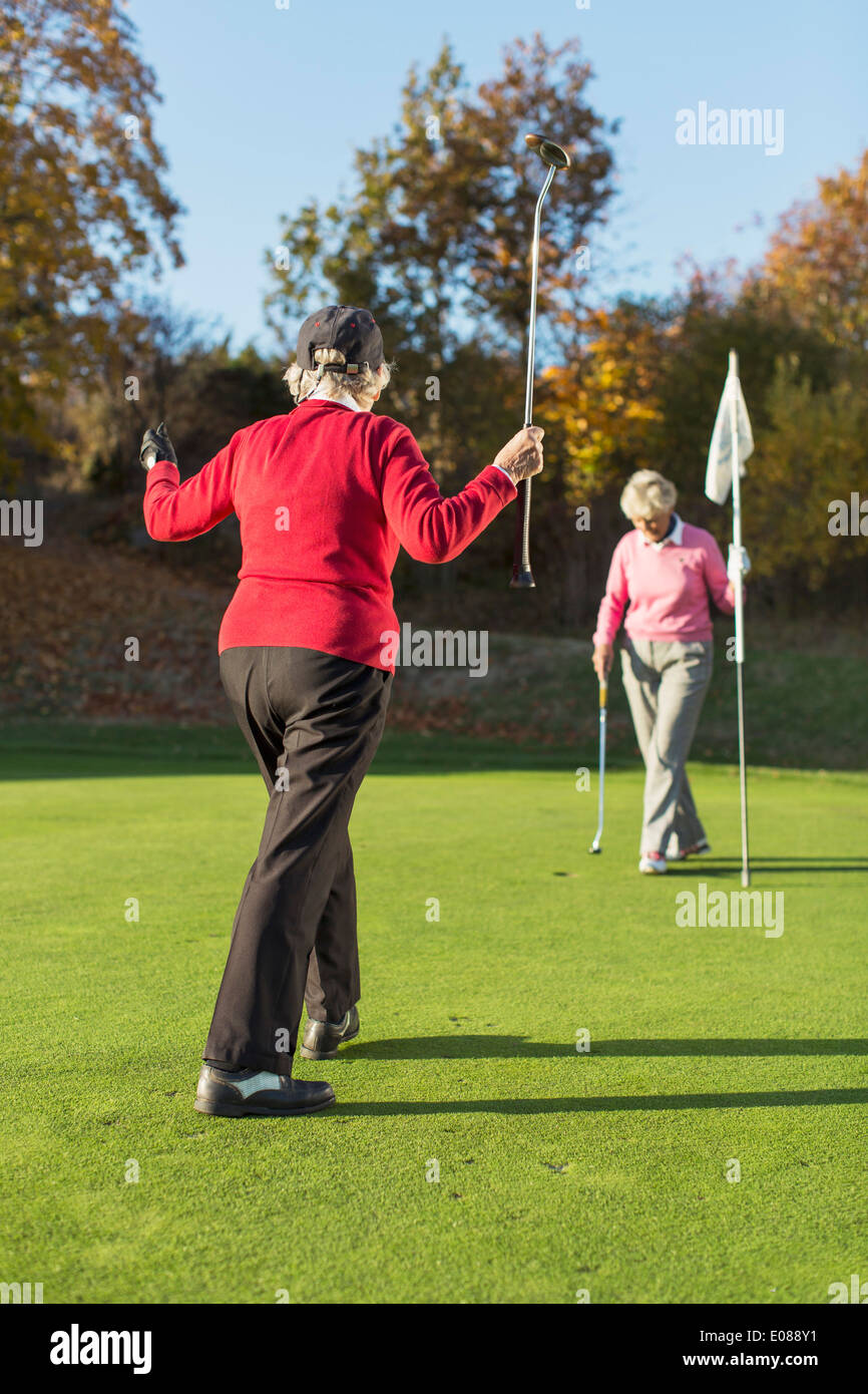 Full length rear view of senior female golfer playing with friend on golf course - Stock Image