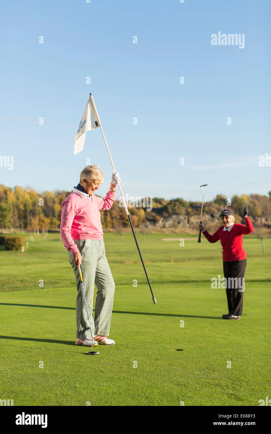 Senior woman celebrating golf shot while friend holding flag on course - Stock Image