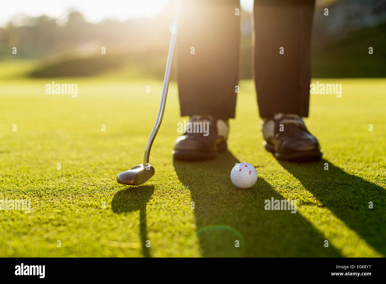 Low section of senior woman putting green on golf course - Stock Image